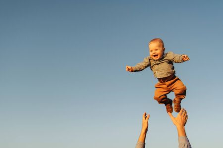 Happy baby boy because his father is throwing him up to the sky. Background of the sky Stockfoto