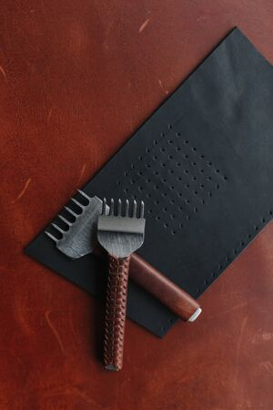 Punches on the leather shred with the place for your text. Leather craft. Handmade
