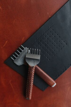 Two punches on the leather shred with the place for your text. Leather craft. Handmade Stock Photo