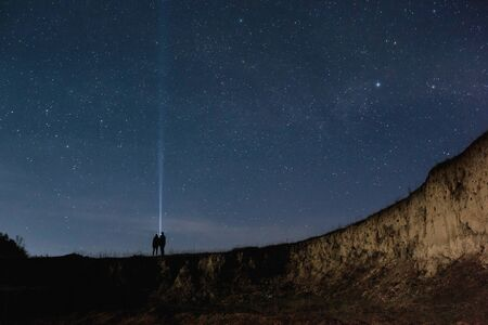 Couple in love holding each other hands under the starry sky. Love story