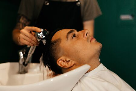 Man washing head in the barbershop. Groom's preparation. Man portrait Stockfoto