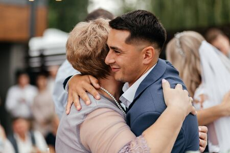 Happy groom emracing his mother during the wedding ceremony. Wedding photography Stock Photo