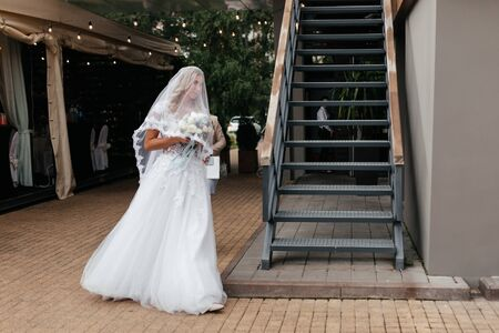 Bride in lace dress and bridal veil going to the wedding ceremony with the bouquet in her hands. Newlywed portrait. Wedding photography