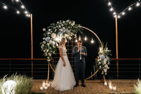 Handsome man saying an oath to the bride from the phone and standing near the circle wedding arch. Newlywed portrait. Wedding photography