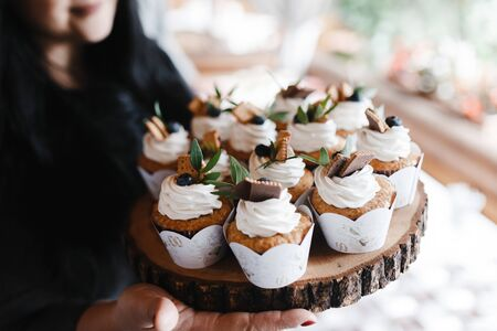 Many cupcakes decorated with cream and berries on the piece of wood. Wedding cupcakes. Dessert Foto de archivo