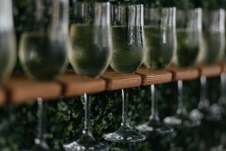 Glasses of champagne on the wooden stand. Alcohol drink. Champagne