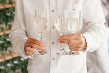 Faceless man wearing white shirt holding three champaagne glasses in his hands
