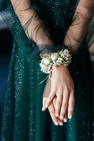 Crossed woman hands at the background of the emerald dress. Bridesmaid hands with nude manicure