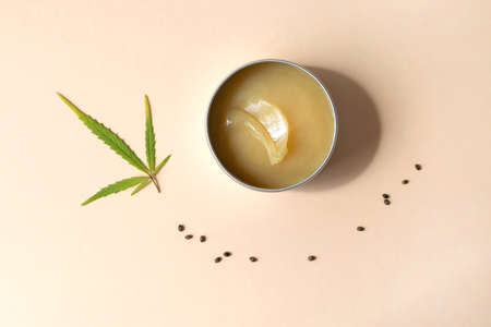 Hemp salve with cannabis leaves on powdery beige