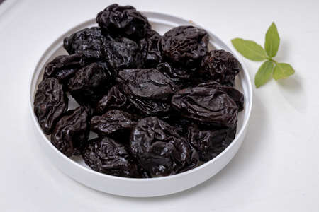 Pitted prunes served on plain white background