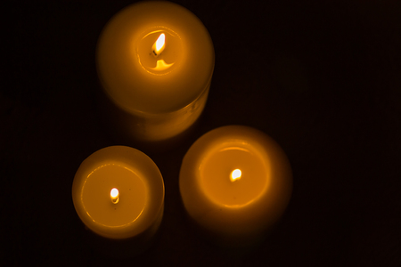a candle is lit in the darkness and gives spiritual warmth Stock Photo