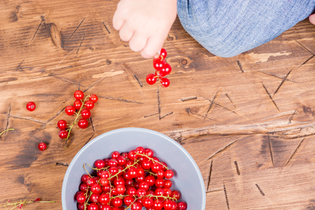 red currants on a wooden background in a hands around all summer blooms