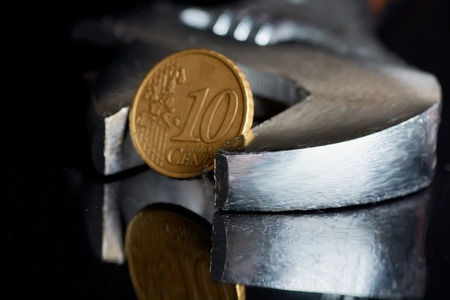 adjustable wrench close-up with Euro cent on black background