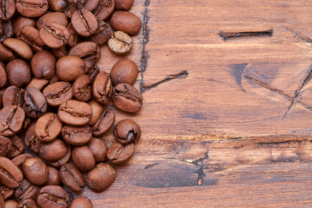 coffee beans on a wooden background scattered from the bag