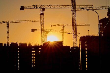 constructie van de bouwkranen in het sterkste licht, anders van de zon
