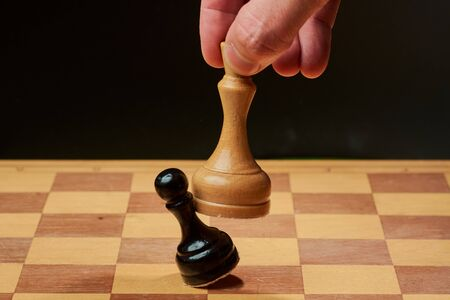 hand of businessman moving chess figure in competition success play. strategy