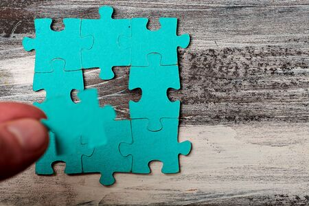 puzzle without details on a wooden background. Stock Photo