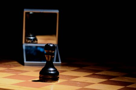 chess piece pawn looks in the mirror and sees the Queen