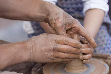 Hands working on pottery wheel. Pottery making.