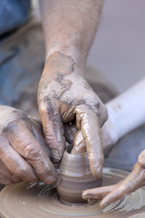 Pottery making. Hands working on pottery wheel.