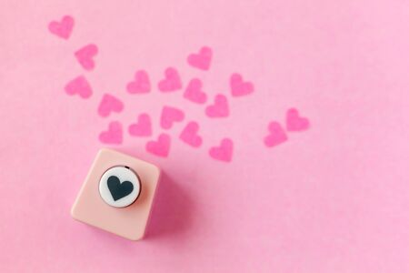 Decoration for Valentine's Day: hole puncher made paper shapes of pink hearts Stockfoto - 134162233
