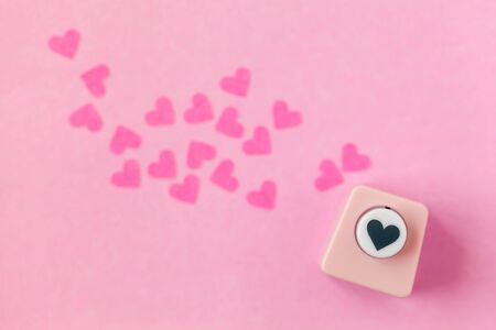 Decoration for Valentine's Day: hole puncher made paper shapes of pink hearts Stockfoto - 134162234