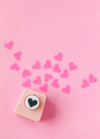 Decoration for Valentine's Day: hole puncher made paper shapes of pink hearts Stockfoto - 134162235