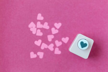 Decoration for Valentine's Day: hole puncher made paper shapes of pink hearts Stockfoto - 134162237