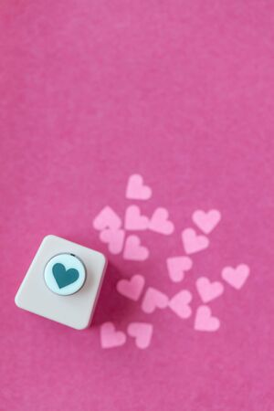 Decoration for Valentine's Day: hole puncher made paper shapes of pink hearts Stockfoto - 134162238