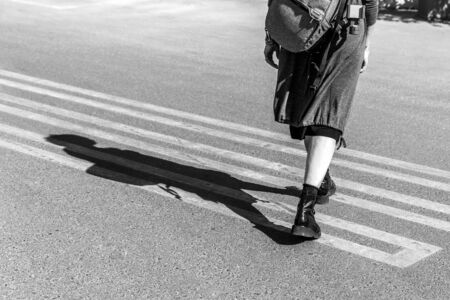 Stylish woman walking on a street, only bottom part of the body showing, shadow on a pedestrian crossing.