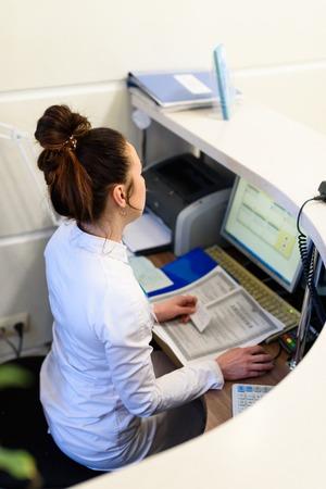 Vrouwelijke receptioniste werken op de computer.