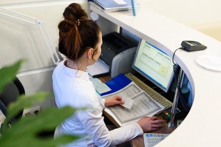 Weibliche Empfangsdame, die den Computer arbeitet. Standard-Bild