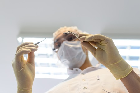 Young man dentist in protection gloves and a mask, keeps dental instrument looking at the camera.