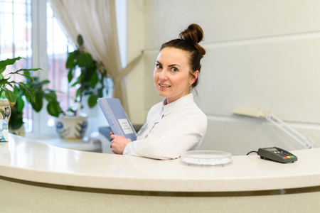 Woman receptionist in medical coat stands at reception desk in hospital. Front view. flat illustration. Dental office interior design with green plants and girl administrator. Clinic registry Stock Photo