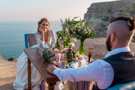 Happy just married young wedding couple celebrating and have fun at beautiful beach sunset in Crimea, Sevastopol.