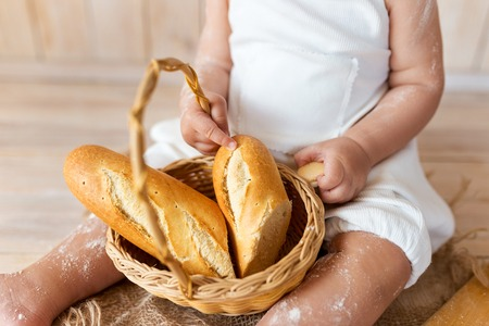 Children hand with bread in bread basket 写真素材