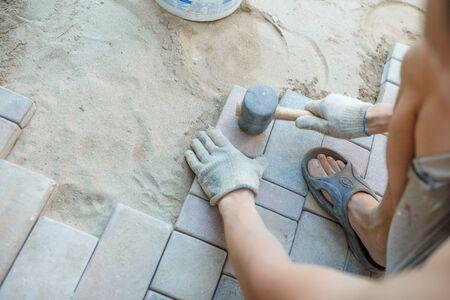 Master puts sidewalk tile. Close-up