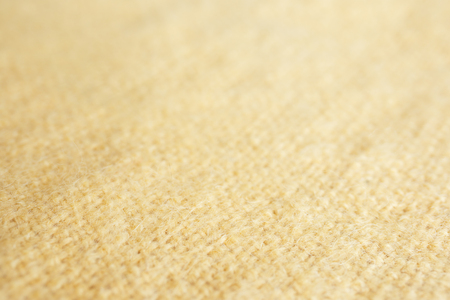 Background blur picture of a soft fur yellow carpet. wool sheep fleece closeup texture background. Fake color yellow fur fabric. top view Stock Photo