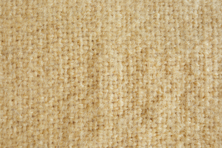 Background picture of a soft fur yellow carpet. wool sheep fleece closeup texture background. Fake color yellow fur fabric. top view