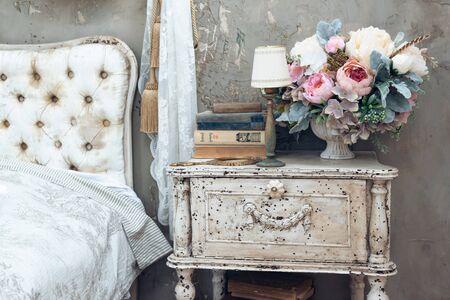 stanza vintage in uno studio fotografico con un tavolo in legno vintage con fiori, specchio vintage e libri. Elementi di stile vintage. Archivio Fotografico