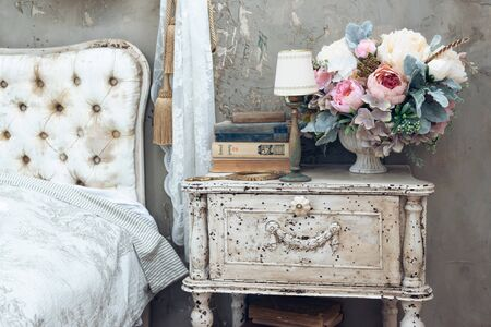 vintage room in a photo studio with a vintage wooden table with flowers, vintage mirrow and books. Elements of vintage style.
