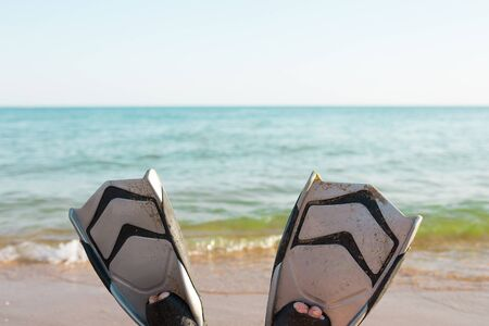 Summer wellness holidays by the sea concept, feet in fins on the beach.