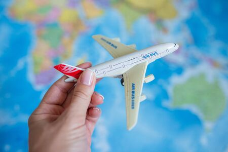The model plane in a women hand on the background of the map. travel, tourism, air travel.