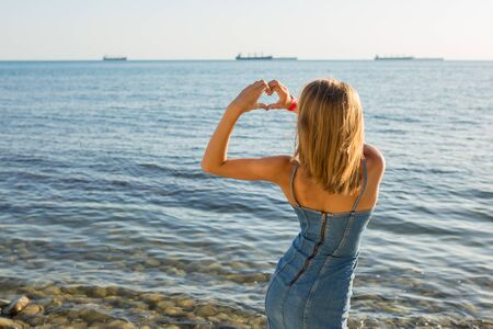 A young girl making heart symbol with her hands on the sea background. Stock Photo