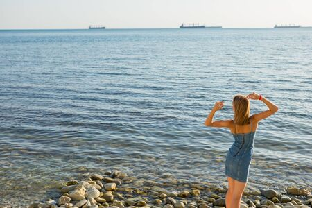 A young girl looking at the sea. Stock Photo