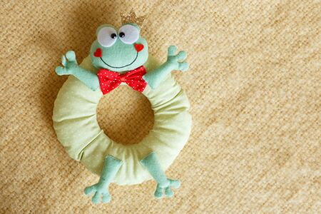 frog soft toy for kids on yellow background.