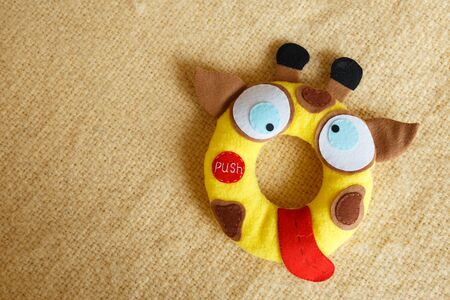 Giraffe soft toy for kids on yellow background.