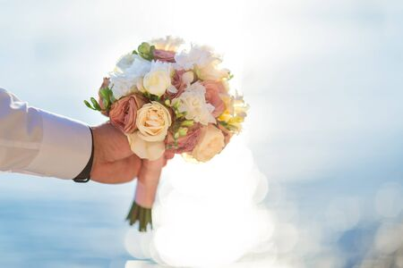 Groom holding bouquet of flowers on the beach. Sea background.