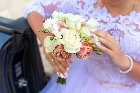 The bride holds a wedding bouquet in her hand against the background of a white dress. Bridal bouquet on the wedding day. Flowers for the bride. A small bridal bouquet close-up. Stock Photo