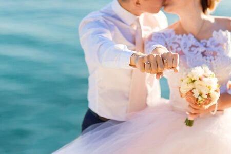 Kissing newlyweds reach out their fists with wedding rings on the the sea background.